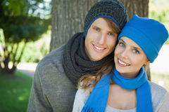 Cute couple smiling at camera in hats and scarves Royalty Free Stock Photography