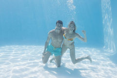Cute couple smiling at camera underwater in the swimming pool Royalty Free Stock Photos