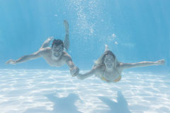 Cute couple smiling at camera underwater in the swimming pool Stock Photo
