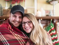 Cute couple snuggled up in winter. Cute young couple cuddled up by the fire in wintertime Royalty Free Stock Photography