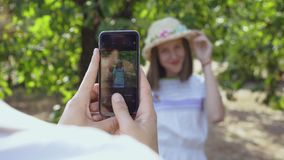 Cute couple spending time together in the park. The man taking photo of pretty woman in hat. Lovers have fun outdoors. Cute couple spending time together in the stock video