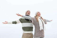 Cute couple standing with arms open wide Royalty Free Stock Images