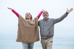 Cute couple standing with arms open wide Royalty Free Stock Photos