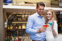 Cute couple standing and drinking cocktails Stock Photo