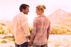 Cute couple standing hand in hand smiling at each other Royalty Free Stock Photography
