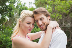 Cute couple standing outside hugging smiling at camera Stock Photo