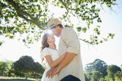 Cute couple standing in the park embracing Stock Photography