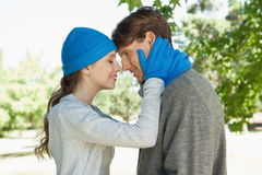 Cute couple standing in the park in hats and scarves Royalty Free Stock Images