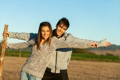 Cute couple stretching arms outdoors. Royalty Free Stock Image