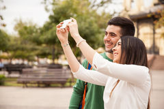 Cute couple taking pictures outdoors. Portrait of a cute young couple using a smartphone to take some pictures during a trip Royalty Free Stock Image