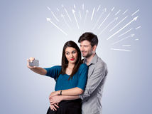 Cute couple taking selfie with arrows Stock Images