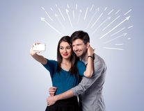 Cute couple taking selfie with arrows Royalty Free Stock Images