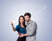 Cute couple taking selfie with arrows Stock Photos