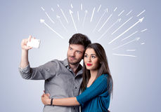Cute couple taking selfie with arrows Royalty Free Stock Photography