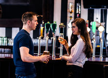 Cute couple talking in a bar. Cute couple talking and having a drink in a bar Royalty Free Stock Photo