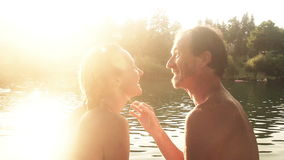 Cute couple talking and laughing while sitting by the river at sunset stock video footage