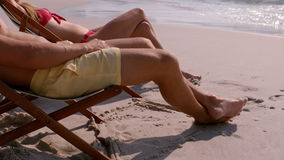 Cute couple tanning together in the deck chair. In slow motion stock video footage