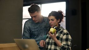 Cute couple of two young attractive people using laptop. Full concentration. Spending time together. Cute couple of two young attractive people using laptop stock footage