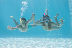 Cute couple underwater in the swimming pool with snorkel and starfish Stock Photography