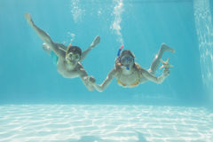 Cute couple underwater in the swimming pool with snorkel and starfish Royalty Free Stock Photo