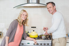 Cute couple using copper kettle Stock Photos
