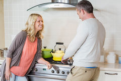 Cute couple using copper kettle Royalty Free Stock Photography