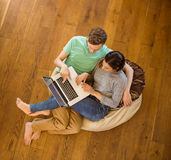 Cute couple using laptop on beanbag Stock Photos