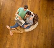 Cute couple using laptop on beanbag Stock Photo