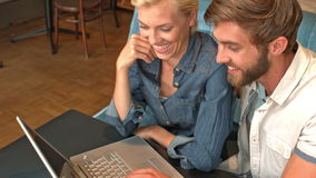 Cute couple using laptop in cafe. In slow motion stock footage