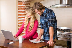 Cute couple using laptop and reading newspaper Royalty Free Stock Images
