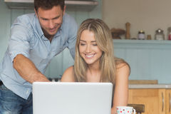 Cute couple using laptop together Stock Photo