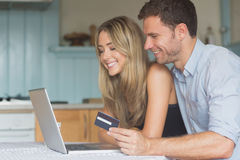 Cute couple using laptop together to shop online Stock Photos