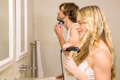 Cute couple using a razor and a straightener Royalty Free Stock Photography