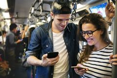 Cute couple using smartphones on the subway stock photography