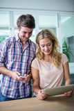 Cute couple using tablet computer in the kitchen Stock Photography