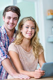 Cute couple using tablet computer in the kitchen Stock Photos