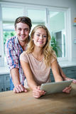 Cute couple using tablet computer in the kitchen Royalty Free Stock Photography