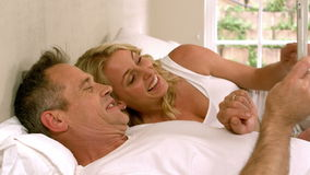 Cute couple using tablet pc. In bed stock video footage