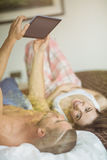 Cute couple using tablet pc in bed Stock Photography
