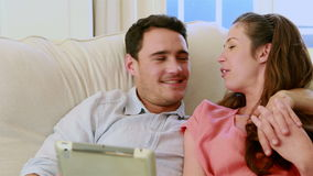Cute couple using tablet pc on the couch stock video footage