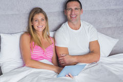 Cute couple using their tablet pc together in bed Stock Photo