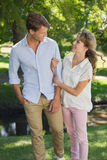 Cute couple walking arm in arm in the park smiling at each other Stock Photo