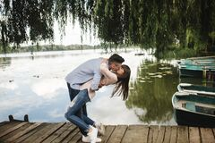 Cute couple walking near water. Girl in a white shirt. Pair by the river. Loving young couple near the river with boats. love