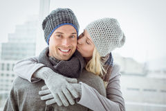 Cute couple in warm clothing hugging man smiling at camera Stock Image