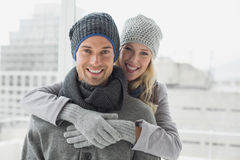 Cute couple in warm clothing hugging smiling at camera Stock Photo