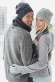 Cute couple in warm clothing hugging smiling at camera Royalty Free Stock Images