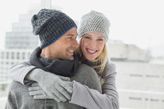 Cute couple in warm clothing hugging woman smiling at camera Stock Image