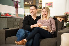 Cute couple watching a comedy on TV Stock Photo