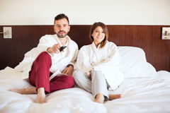 Cute couple watching TV at a hotel Stock Image