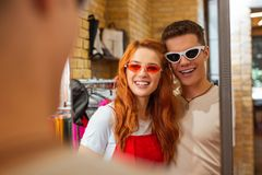 Cute couple wearing funny sunglasses and kindly smiling. Adorable couple. Beautiful young loving couple looking at their reflection in the mirror while doing royalty free stock photo